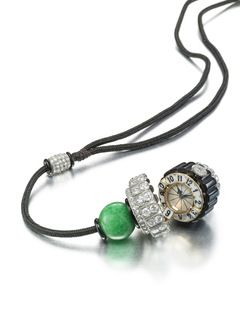 acorn form, suspended from a cord with a dimaond-studded  slide link, fastened through a boule of jade above a lid of diamonds, opening to reveal a watch with black enamel numerals on white enamel plaques around a  dial with blued steel hands, all above onyx fluted gadroons with diamond-set bezel, above a bottom ring of diamonds