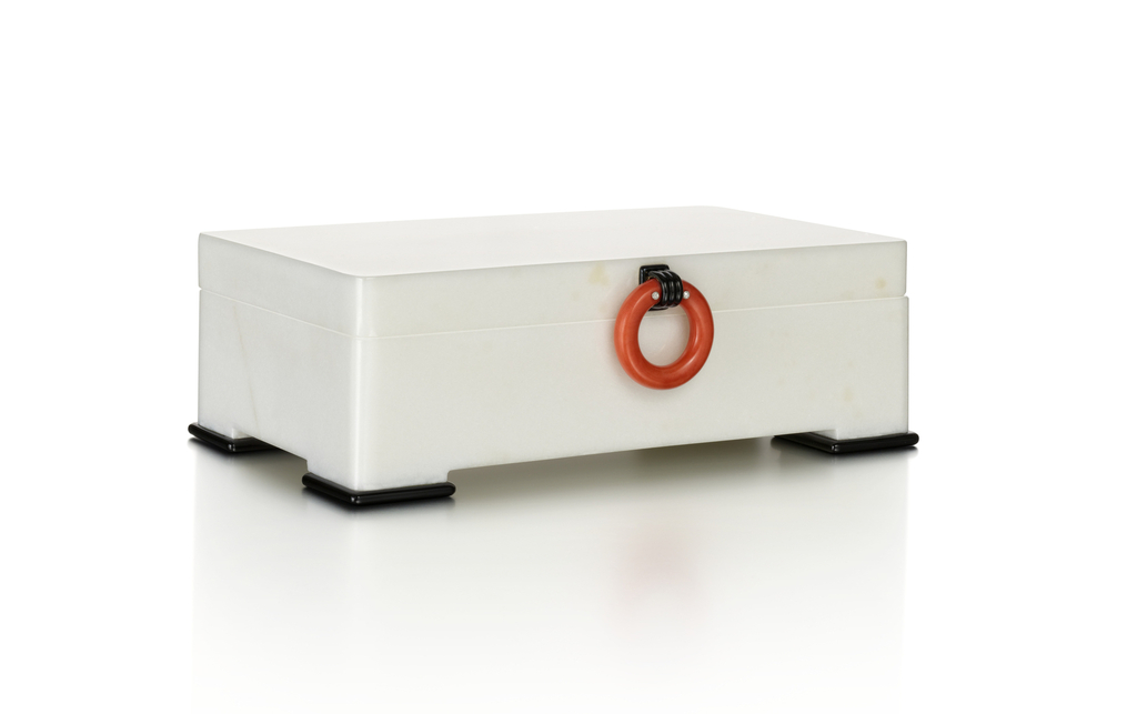 Box of white marble decorated with a coral ring handle with rose-cut diamonds and held within a black enamel mount, with three red and black enamel and diamond hinges, standing on four onyx feet