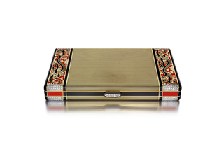 Rectangular vanity case, the front and back centered with small black enamel bands with borders of rectangular sections depicting dragons and floral vines, sides applied with black and red enamel sections, diamond-set thumbpiece; interior fitted with mirror, powder compartment, and larger open compartment