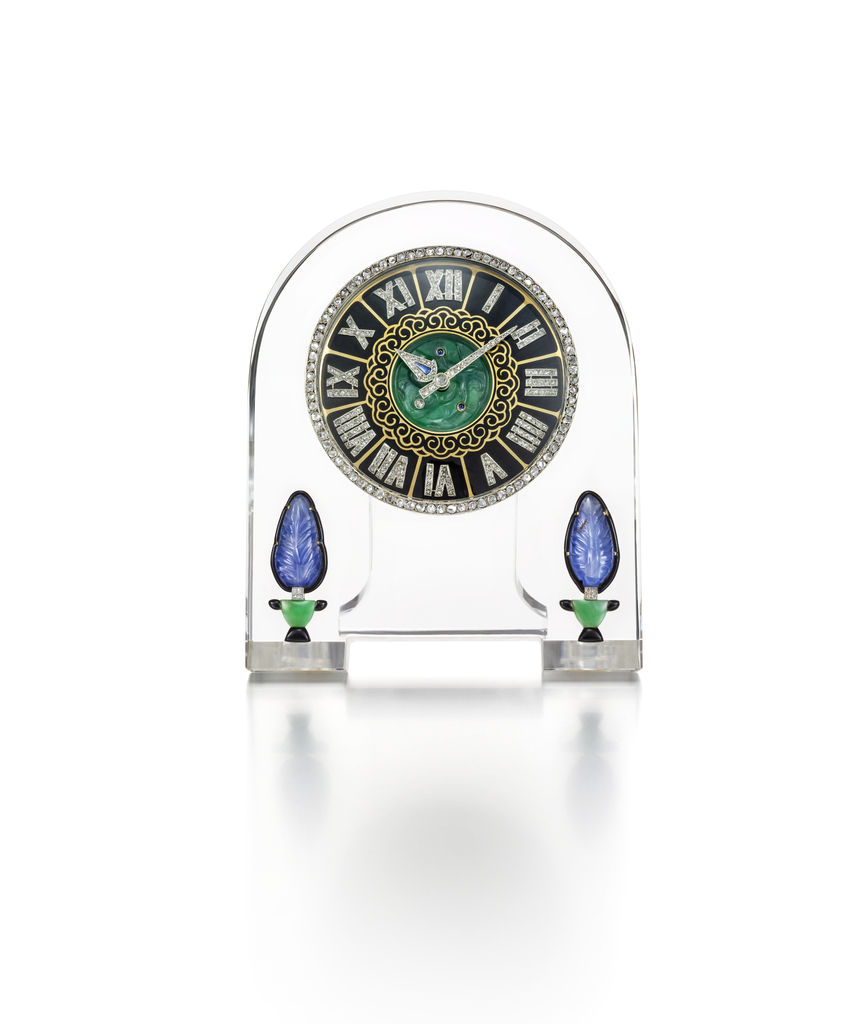 Clock composed of an arched rock crystal panel with circular dial centered by a carved jade medallion embellished with cabochon sapphires and diamond, within a gold and black enamelled chapter ring with rose-cut diamond-set Roman numerals and diamond and sapphire hands, encircled by a rose-cut diamond bezel, further decorated with a pair of topiary motifs formed of carved sapphires and leaves of jade, and black enamel, mounted in platinum and gold, with red leather fitted case by Cartier