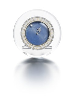 Eight Day Clock composed of a circular rock crystal mount with round dial of sky blue guilloché enamel in a ray pattern, the rotating rose diamond stars indicating the hour, the chapter ring of white champlevé enamel featuring Roman numerals alternating with rosettes, the bezel set with rose-cut diamonds, folding rock crystal strut back, mounted in platinum, with fitted leather Cartier case