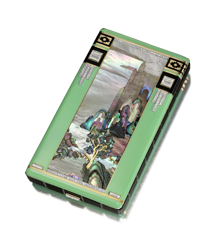rectangular with green enamel around a mountain landscape with river and trees, with black enamel and diamond details, black onyx side rectangles with diamond-set button clasp, the interior fitted with mirror, two powder compartments, lipstick holder in gold