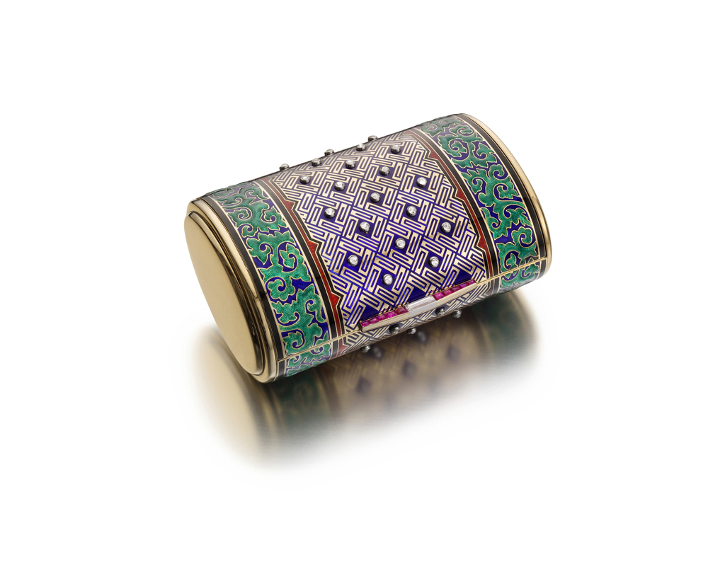 in Chinese taste, of cylindrical drum form, enamelled in blue and green continuous foliate panel around a blue and gold geometric central panel studded with diamonds, and with red border, the blade-form thumbpiece with rubies and diamonds,gold drum ends