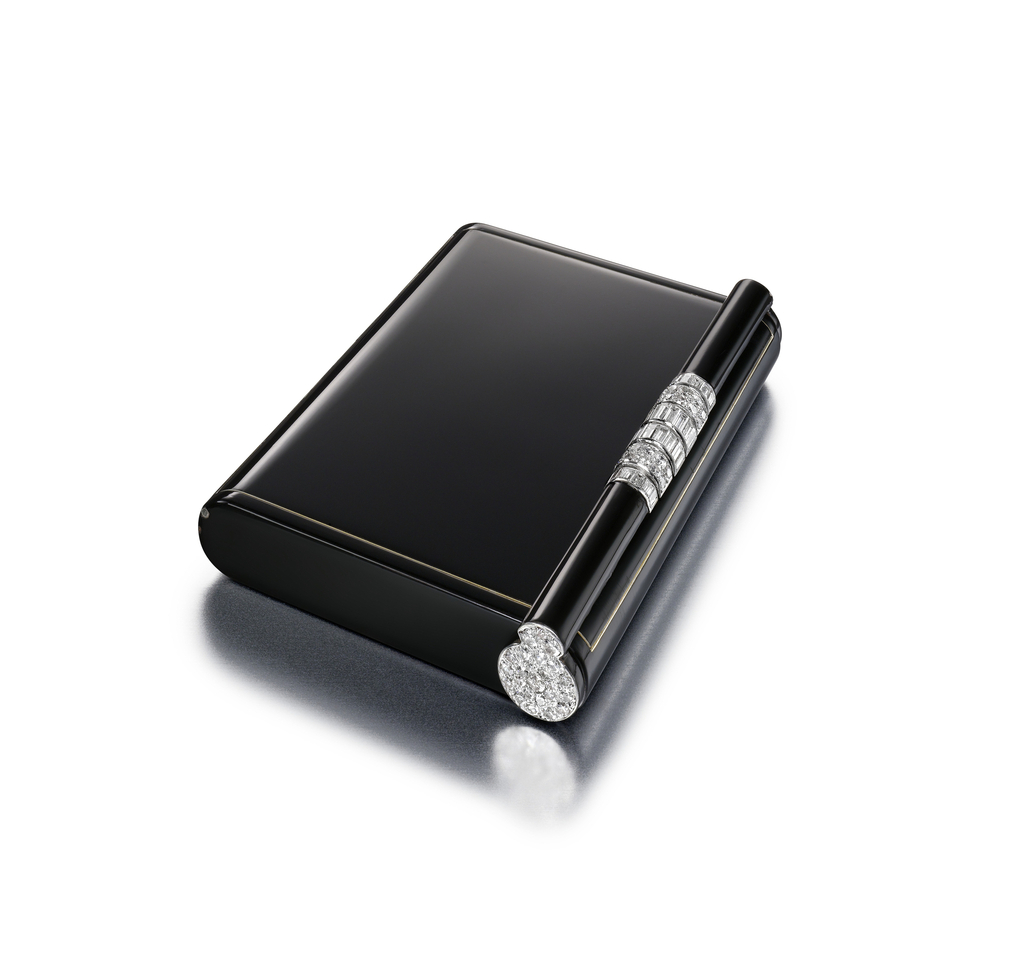 Vanity case in black enamel, the thumbpiece designed as a roll-down bar set with baguette and rose-cut diamonds; interior with fitted mirror and two covered compartments