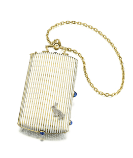 Vanity case with curved ends suspended from an oval link gold chain; front of case shows lines of  seed pearls accented with a lattice motif set with diamonds, accented by a small rabbit; cabochon sapphire as thumbpiece; interior fitted with a mirror and writing pad; powder compartment fitted with two lipstick holders with a removable pencil