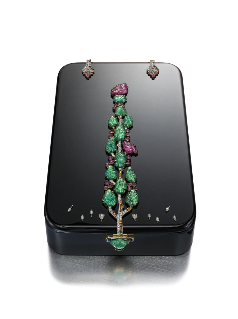 rectangular with rounded corners, a central cypress tree of emeralds with ruby birds , the clasp as a pot overhanging the edge.