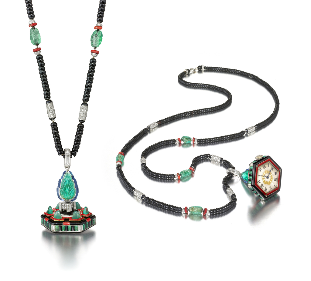 hexagonally shaped case, with emerald and baguette diamonds set in platinum, the back rising to a pyramid and attached to a beaded onyx cord set with emeralds , coral and diamonds at interval.