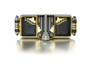 Miniature compact brooch, the front with black enamel geometric and zigzag pattern, accented in the center by a diamond-set band terminated by a diamond plaque, the sides accented by gold bars applied with black enamel bands and set with cabochon sapphires; fitted mirror and two compartments, surmounted by a small compartment
