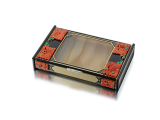 Cigarette case featuring semi-transparent rectangular agate panels on the front and back surrounded by black enamel, accented on the corners and sides by carved coral segments with cabochon emeralds, the back applied with black enamel stripes around an agate panel, two sides composed of carved onyx segments, with diamond-set thumbpiece