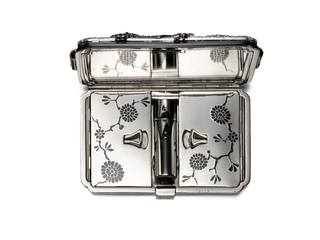 Vanity case with inverted corners depicting a stylized nature scene of chrysanthemums composed of rubies, amethysts, sapphires, and emeralds on a diamond trellis, outlined in diamonds with diamond-set handles, on a field of black enamel; the reverse and interior of the case in white gold decorated with black enamel chrysanthemums, diamond-set push button clasp; interior with fitted mirror, lipstick holder, and two powder compartments; mounted in white gold