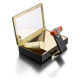 Vanity case in black enamel, with a black enamel hinged strap that works as a clasp accented by a carved coral baton enhanced by diamonds; interior with fitted mirror, powder compact, and detachable lipstick holder