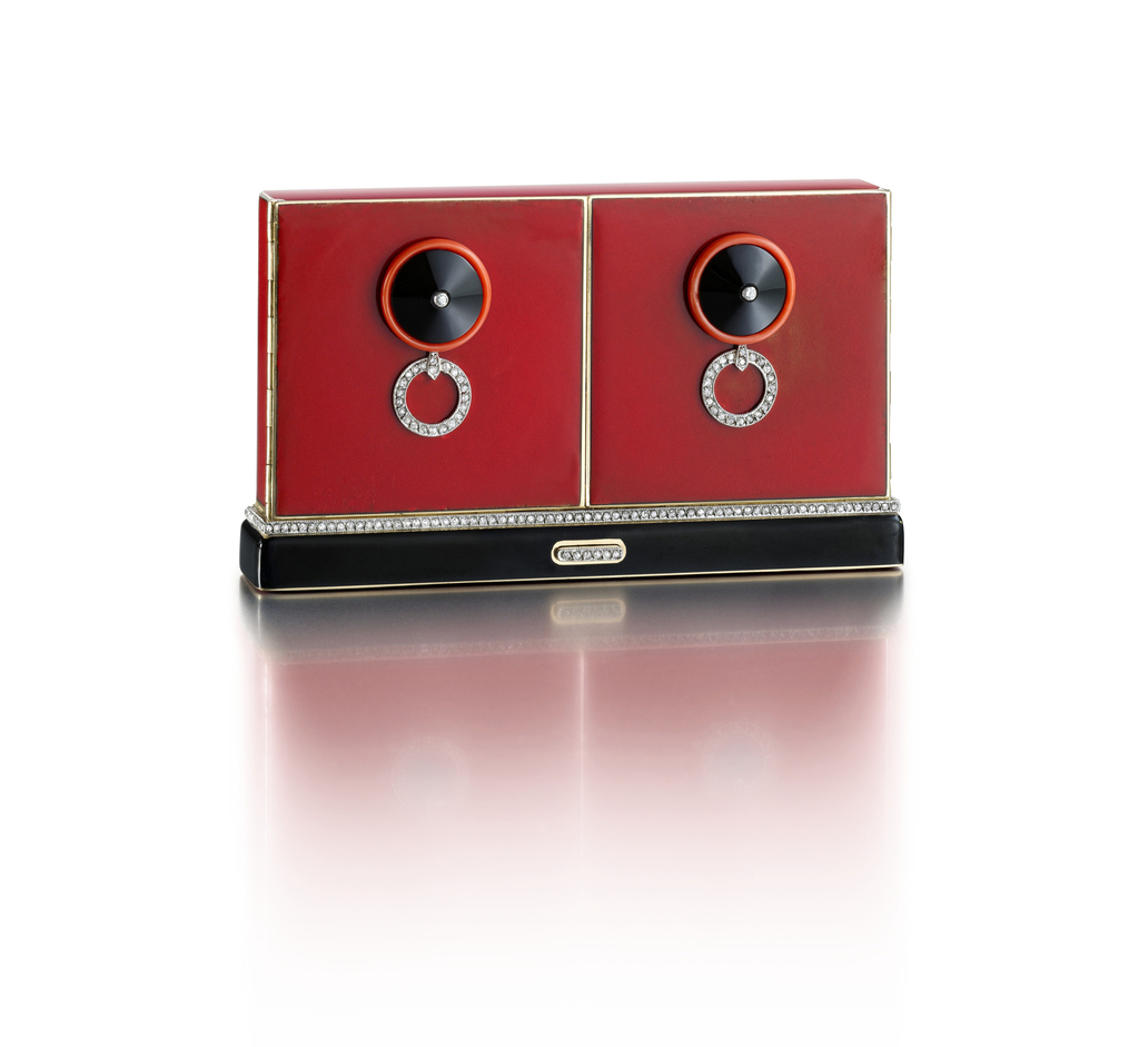 Vanity case in the form of two doors, with red and black lacquer, the front featuring two circular door-handle motifs of carved onyx and coral studded with diamonds, supporting diamond-set rigns, the base accented by a band of diamonds, with diamond thumbpiece; interior fitted with two mirrors and two compartments