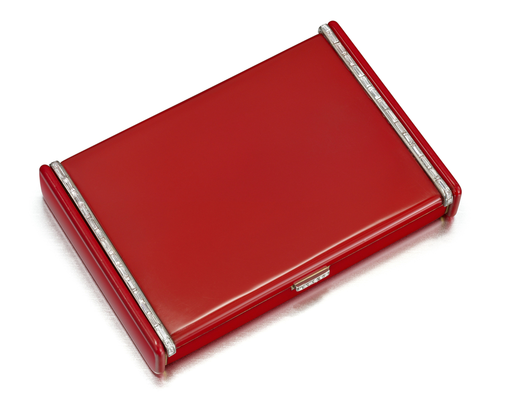 Vanity case in red enamel, with raised edge on left and right sides with diamond-set bands, pushpiece set with rose-cut diamonds; interior with fitted mirror, powder compartment, and detachable lipstick holder