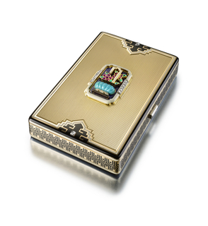 Vanity case composed of ribbed gold, the front accented by a central placque depicting a carved turquoise pot, ruby flowers, and emerald leaves against a dark blue enamel background and framed by white enamel and diamonds, the front and back bordered by black and white enamel bands, with pagoda-shaped black and white enamel accents set with square-cut diamonds, sides decorated in a black enamel geometric pattern, with diamond-set thumbpiece; interior with fitted mirror, powder compartment, and detachable lipstick holder