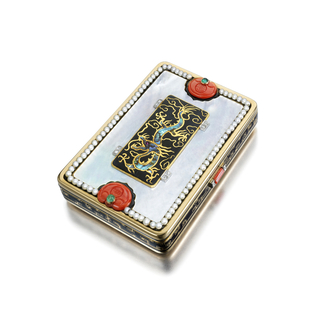 rectangular with rounded angles, the gold body mounted with mother-of-pearl panels on front and back, the lid bordered by black enamel and small, natural pearls, the center with black enamel decorated with the figure of a dragon set within four sets of rose-cut diamonds, the ends with two corals carved with a Ruyi centered by cabochon emeralds, the sides enamelled in black with gold dragon designs centered by a coral thumbpiece, the interior with fitted mirror and powder compartment.