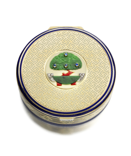 Circular compact centering a bonsai tree of carved jadeite greenery with cabochon sapphires and red enamel trunk in a carved jadeite pot, with red enamel feet and rose-cut diamond handles, the compact further applied with a cream-colored enamel geometric pattern within a blue enamel border, the sides of ribbed gold with white enamel geometric pattern within diamond-shaped frames