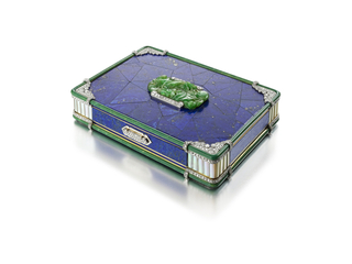 Cigarete case decorated with lapis lazuli marquetry with a green enameled reed border, the lid applied with a carved jade segment of scrolling foliate motif, the sides of lapis lazuli with blue enamel stripes, the corners of mother-of-pearl and round diamonds; mounted in gold and platinum