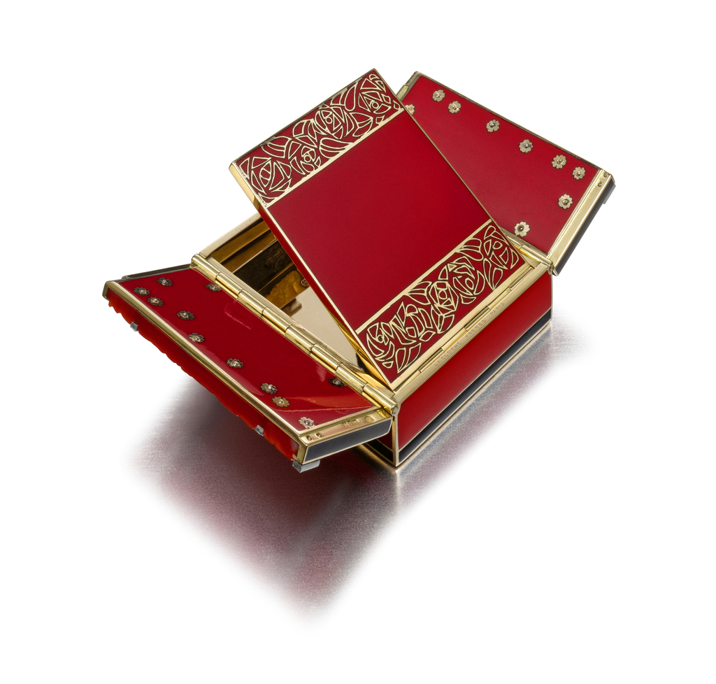 Rectangular compact of red and black lacquer, the front composed of a carved amber lid inlaid with carved coral sections of rose design, studded with diamonds, intersected by two bands of diamonds, flanked by black lacquer stripes and diamond accents, with sugarloaf cabochon coral thumbpiece framed by diamonds; interior opens to reveal a red lacquer surface with bands of stylized roses and the sides of gold flowerheads set with diamond centers, beneath the fitted mirror and compartment; with matching lipstick baton with detachable lipstick holder, set at each end with a pearl