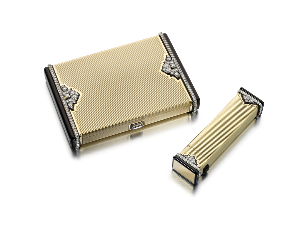 A cigarette case composed of ribbed yellow gold, accented at either end with raised edges applied with black enamel enhanced by stylized pamette motifs completed by diamond bands, with diamond push piece; with matching lighter