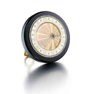 desk clock with a circular black onyx mount with a guilloché enameled dial patterned to resemble rays of light, the hands replaced by rose-cut diamond-set stars, the chapter ring featuring chased gold Roman numerals, and rosettes on a white champlevé enamel platinum, with original red leather fitted case by Cartier