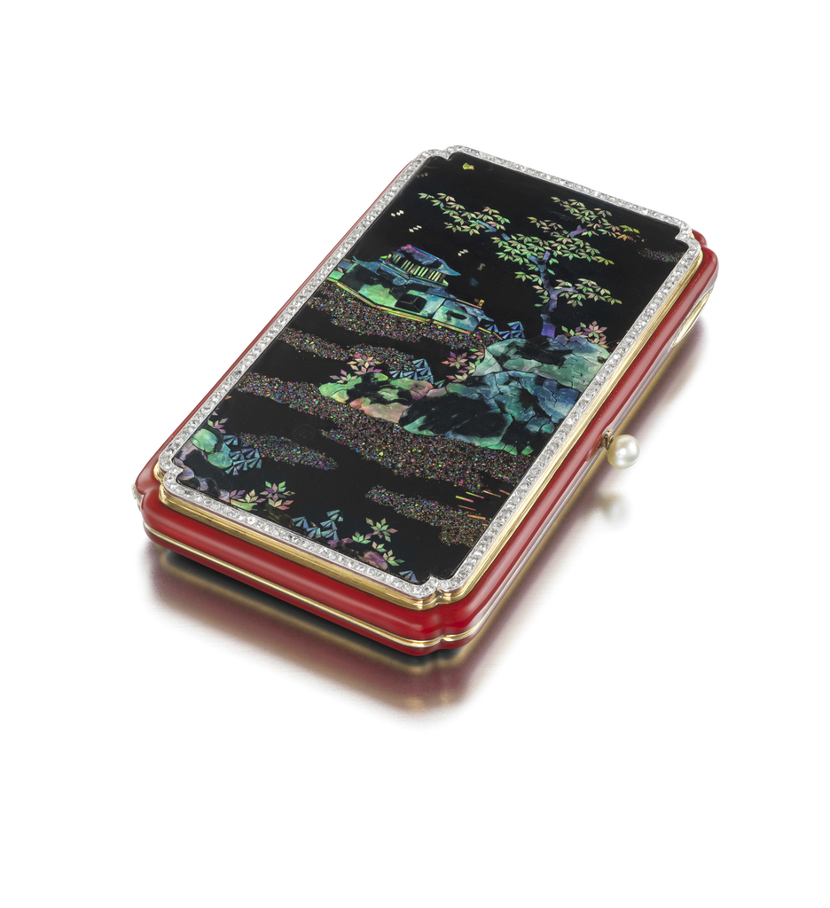 Vanity case with inverted corners, the front depicting a Chinese garden, composed of black lacquer inlaid with shell, framed by a diamond border, the sides and back applied with red enamel, with pearl thumbpiece; interior with fitted mirror, powder compartment and detachable lipstick holder