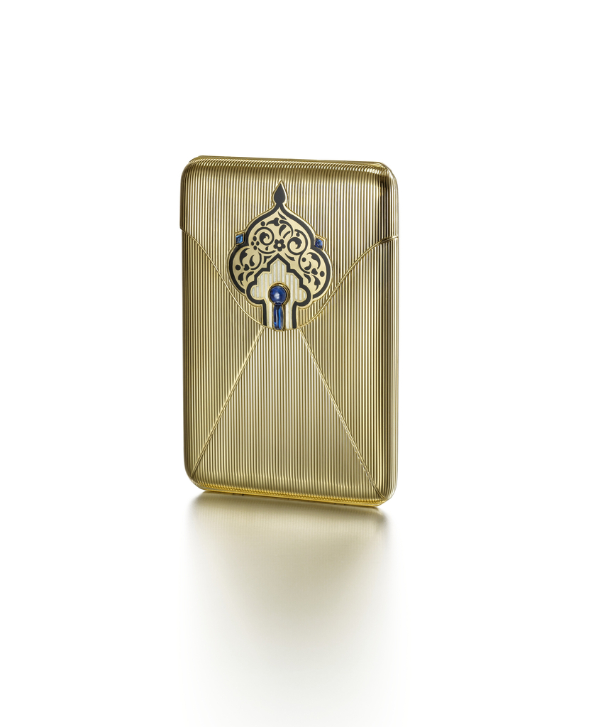 Rectangular case of rubbed gold designed as an envelope with hinged lid embellished with a stylized Persian-style palmette, interior with a holding bar for cigarettes