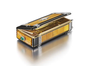 Vanity case of black enamel, the front set with an amber plaque centering a diamond-set Chinese symbol, enhanced by a meander pattern of diamonds at the top and bottom, one end featuring a diamond-set stylized pagoda roof; interior fitted on one side with a mirror and two compartments, the other side opening to reveal a cigarette case and match holder