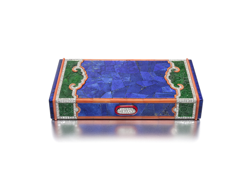 Vanity case with lapis lazuli marquetry on the central panel, the edges decorated with carved jade panels with carved ruyi outlined by round diamond and coral borders of scrolling cloud shapes, the pattern continues around to the reverse, coral rims applied to the edges, the short ends set with lapis lazuli panels, the diamond-set button clasp encircled by red lacquer; interior with fitted mirror, two powder compartments with powder puffs, and lipstick holder