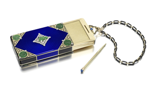 Rectangular sliding vanity case centering upon blue guilloché enamel, the four corners accented by circular carved jadeite discs with diamond accents over a gold and black enamel background, the center placque depicting a carved jadeite buddha within an ornate lozenge frame of diamonds, with a cabochon sapphire thumbpiece, suspended from a black enamel and gold chain; interior section slides out of the case from the top revealing a writing tablet, mirror, compartment, detachable lipstick holder, and removable pencil