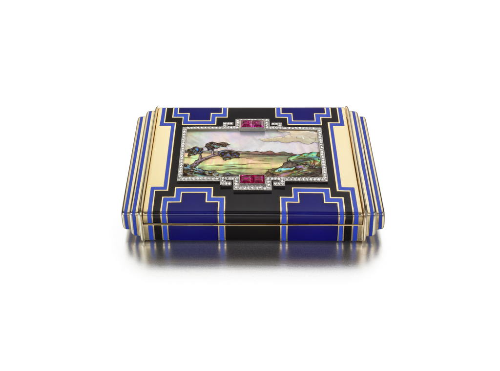 Vanity case with stepped sides, the central mosaic composed of various shades of mother-of-pearl depicting a tree in front of a lake with a mountain range and clouds, framed by an ornate geometric border set with rose-cut diamonds and square-cut rubies, further accented on the front and back with a geometric pattern of light and dark blue and black enamel; interior with fitted mirror, powder compartment, and detachable lipstick holder
