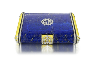 "Vanity case composed of lapis lazuli with yellow enamel sides, decorated on the front with a diamond-set monogram with the letters ""CS"" within an ornate frame, bordered by a diamond trim, the four corners enganced by diamond-set acents, with a yellow enamel thumbpiece accented by a diamond-set openwork placque; interior with fitted mirror, powder compartment, and removable rouge holder"