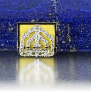 """Vanity case composed of lapis lazuli with yellow enamel sides, decorated on the front with a diamond-set monogram with the letters """"CS"""" within an ornate frame, bordered by a diamond trim, the four corners enganced by diamond-set acents, with a yellow enamel thumbpiece accented by a diamond-set openwork placque; interior with fitted mirror, powder compartment, and removable rouge holder"""