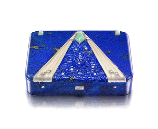 Lapis lazuli box with rounded corners, centering a triangular panel of carved lapis lazuli flowers with diamond centers, sided by triangular fluted frosted rock crystal segments accented with lozenge-shape calibré-cut diamonds, two sugarloaf jadeites at the corners, diamond-set button clasp, mounted in white gold