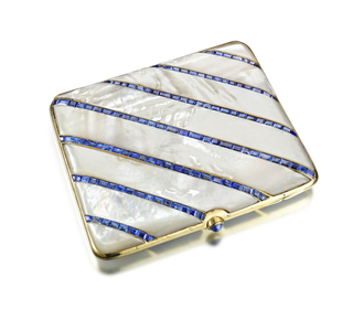Cigarette case composed of alternating diagonal bands of sapphires and mother-of-pearl segments, reverse composed of diagonal mother-of-pearl segments, thumbpiece set with cabochon sapphire; interior fitted with an elastic cigarette band