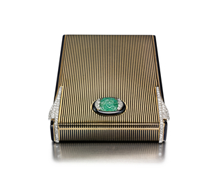 Vanity case with alternating black enamel and polished gold stripes, with black enamel sides, the central motif set with a carved cabochon emerald of floral design, accented by diamonds and a black enamel border, flanked by curved diamond-set tabs to open the case; interior fitted with a mirror and two compartments