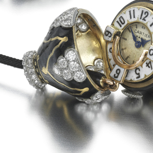 A watch with a circular dial with white enameled chapter ring, black enameled Arabic numerals and blued steel hands, within an acorn-form case decorated with single-cut and rose-cut diamonds on a black enameled ground, suspended from a black silk cord with black enamel and diamond cylindrical slide; mounted in 18-karat gold and platinum