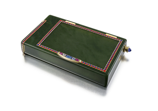 Rectangular nephrite case with a front compartment for cigarettes and a side compartment for matches with a striking surface under the lid, each accented by a red and blue enamel ropework pattern on gold, the front thumbpiece set with sapphire and ruby, the side set with one flat sapphire, with a detachable fluted gold pencil set at the top with a cabochon sapphire