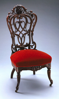 Shaped back, curved in plan, with openwork design of laminated wood in plain and foliate scrolls, and carved bunch of flowers at top.  Carving on front of apron; turning on outcarving front legs, which are fitted with casters.  Seat upholstered in blue silk damask (not original).