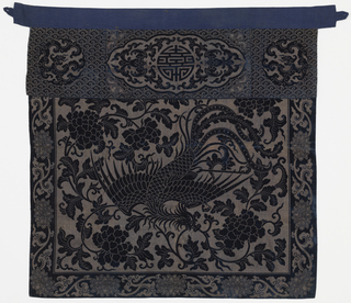 Flying phoenix holding curving sprays of tree peony in deep blue cut velvet on a rectangular foundation of tarnished gold. Border of stylized lotus and leaves reserved in gold on deep blue cut velvet ground. Narrow horizontal panel overlaid across top with two vertical pleats. Circular dragon medalliions flanking lobed central medallion with lucky monogram. Faced with blue cotton.