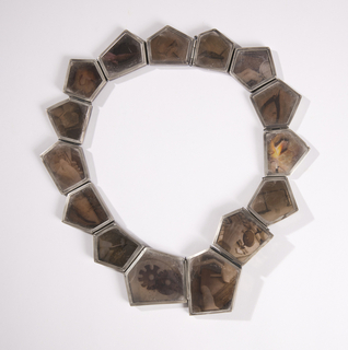 "Necklace comprised of 15 individual polygonic cells of different shapes and sizes, each containing a photographic transparency ""sandwiched"" between two plates of clear mica and enclosed by silver frames."