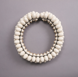 Necklace composed of several layers of off-white oblong gourd-like forms.