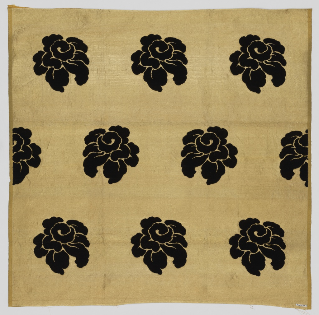 Staggered horizontal repeat of large scale stylized roses. Black roses are on a metallic ground.