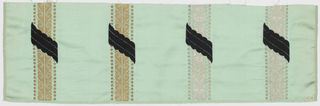 Sample of pale green satin has vertical gold and silver stripes in a scroll pattern banded by dots. Stripes are crossed diagonally with small scalloped bands of black weft velvet.