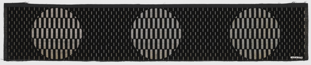 Black cloth ground with silver. Background has all-over design of minute voided vertical rectangles. Large-scale staggered horizontal repeat of circular medallion filled with small vertical rectangles alternately velvet and ground fabric.