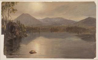 View of a lake with two mountain peaks at left and right and a mountainous ridge in the central distance. The mountains are reflected in the lake which is ringed with trees and foliage. The left a large rock sits at the edge of the lake in front of a slender tree. At left foreground, a smaller rock is submerged in the lake.