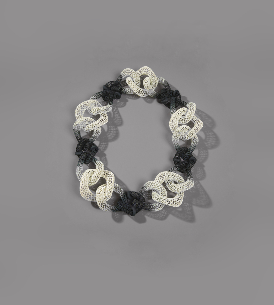 Flexible neckpiece formed of biomorphic hollowed rings of a black and white gradient with hexagonal 'honeycomb' patterning interlocked together.