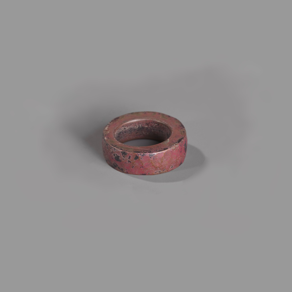 Thick slightly irregular circular ring; rough, patinated surface in shades of dull copper to black .