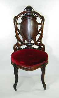 Shaped back, curved in plan, with ovoid escutcheon surrounded by openwork design of laminated wood in scrolls; cabriole legs, the front pair fitted with castors. Upholstered in comtemporaneous machine-woven fancy compound satin. Pressed, steamed, laminated in layers, then glued together at right angles; with an applied crest.