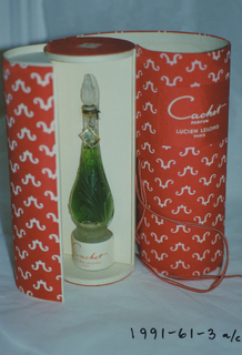 """Clear elongated pear-shaped glass bottle (a) with circular foot; acanthus leaf decoration molded into body and ovoid cap (b). Packaging (c/e) comprising white cardboard cylinder covered in red and white textile printed with repeat of logo; applied label: """"Cachet (in script) / PARFUM /LUCIEN LELONG / PARIS,""""; bottle rests on small cylindrical cardboard stand printed in red with """"Cachet (in script) /LUCIEN LELONG / PARIS"""". Red silk cord wrap."""