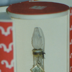 "Clear elongated pear-shaped glass bottle (a) with circular foot; acanthus leaf decoration molded into body and ovoid cap (b). Packaging (c/e) comprising white cardboard cylinder covered in red and white textile printed with repeat of logo; applied label: ""Cachet (in script) / PARFUM /LUCIEN LELONG / PARIS,""; bottle rests on small cylindrical cardboard stand printed in red with ""Cachet (in script) /LUCIEN LELONG / PARIS"". Red silk cord wrap."